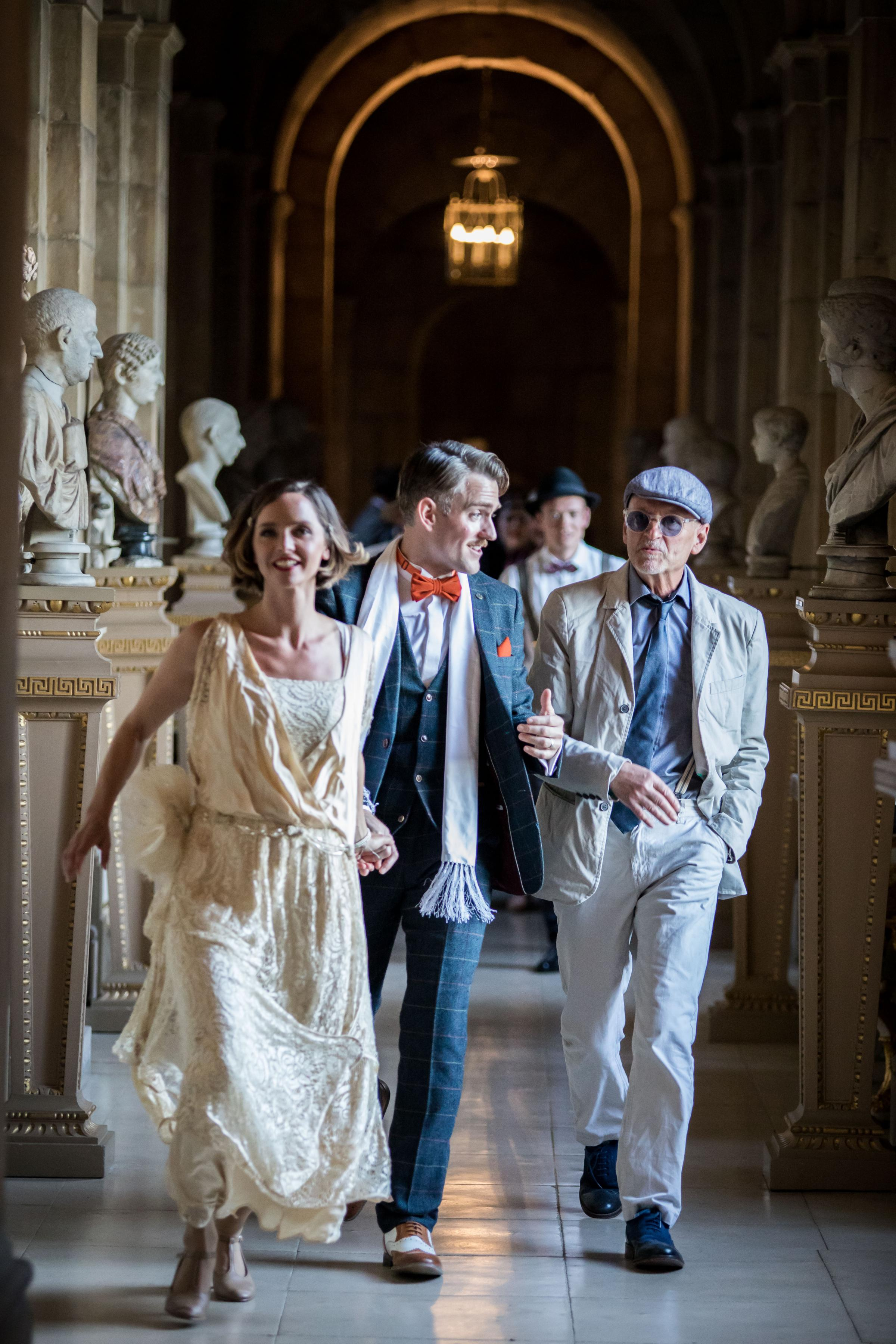 Amie Burns Walker's Daisy Buchanan and Cornelius Geaney Jnr as Tom Buchanan with a party reveller at The Great Gatsby at Castle Howard