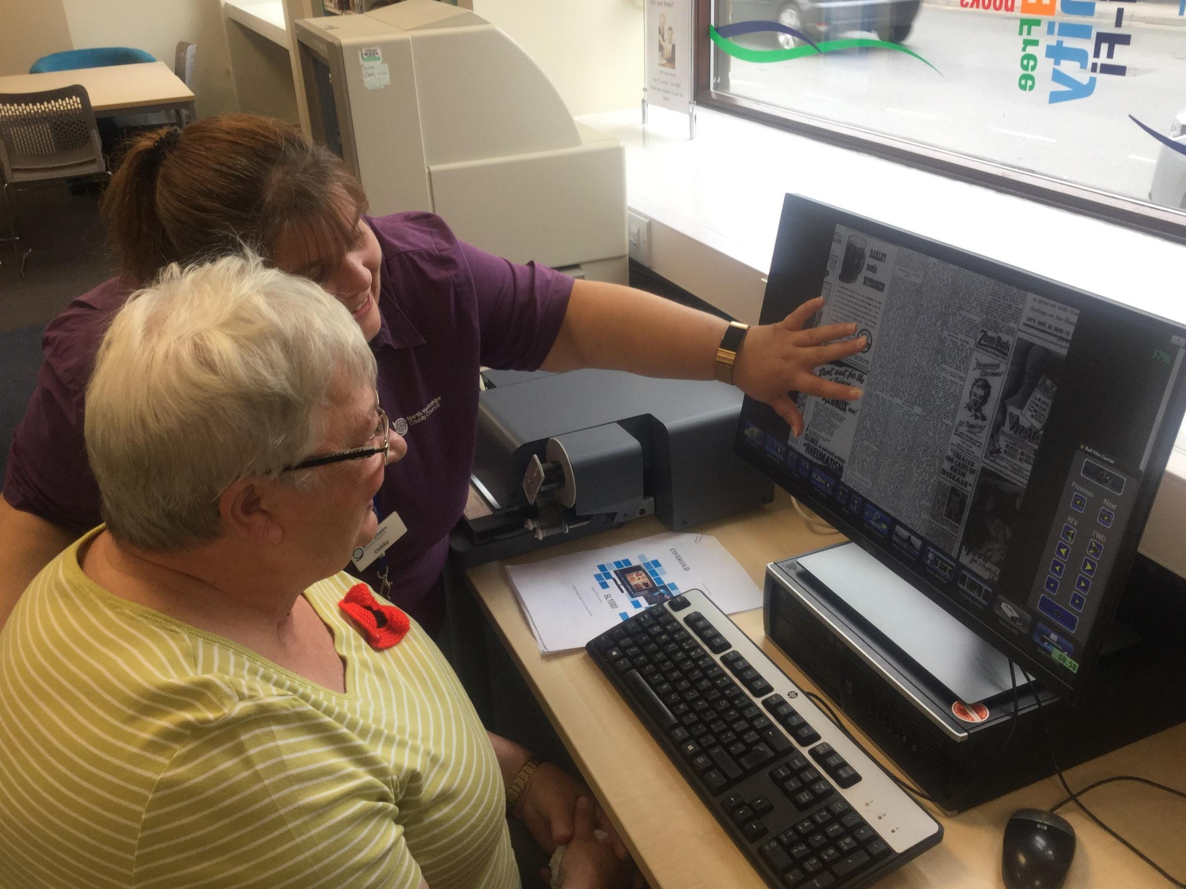 Library staff member Debby Foulkes demonstrates one of the new scanners to a customer.
