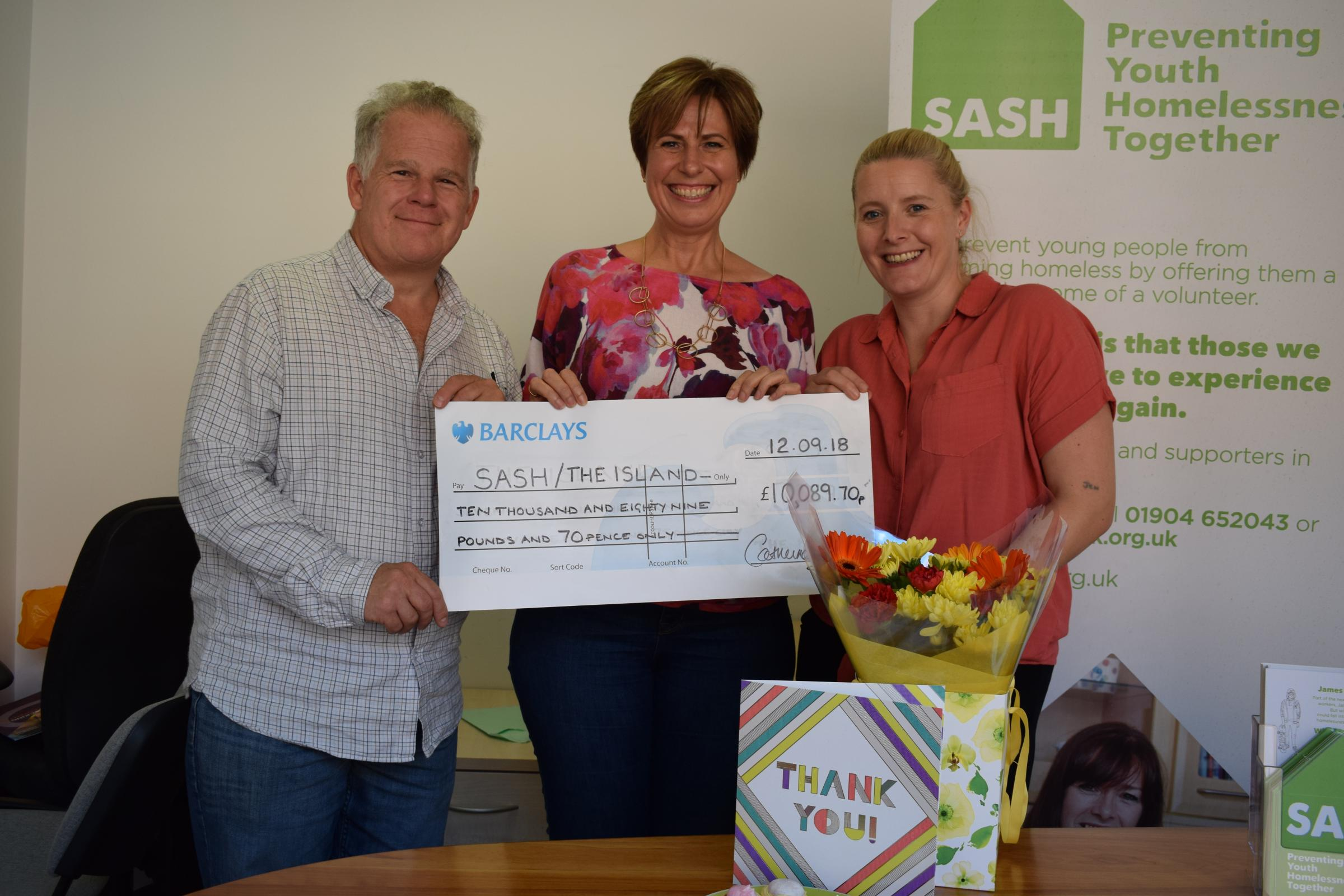 Catherine Adamson, centre, hands over £10,000 raised through fundraising to Nigel Poulton of The Island and Jenna Goodridge from SASH