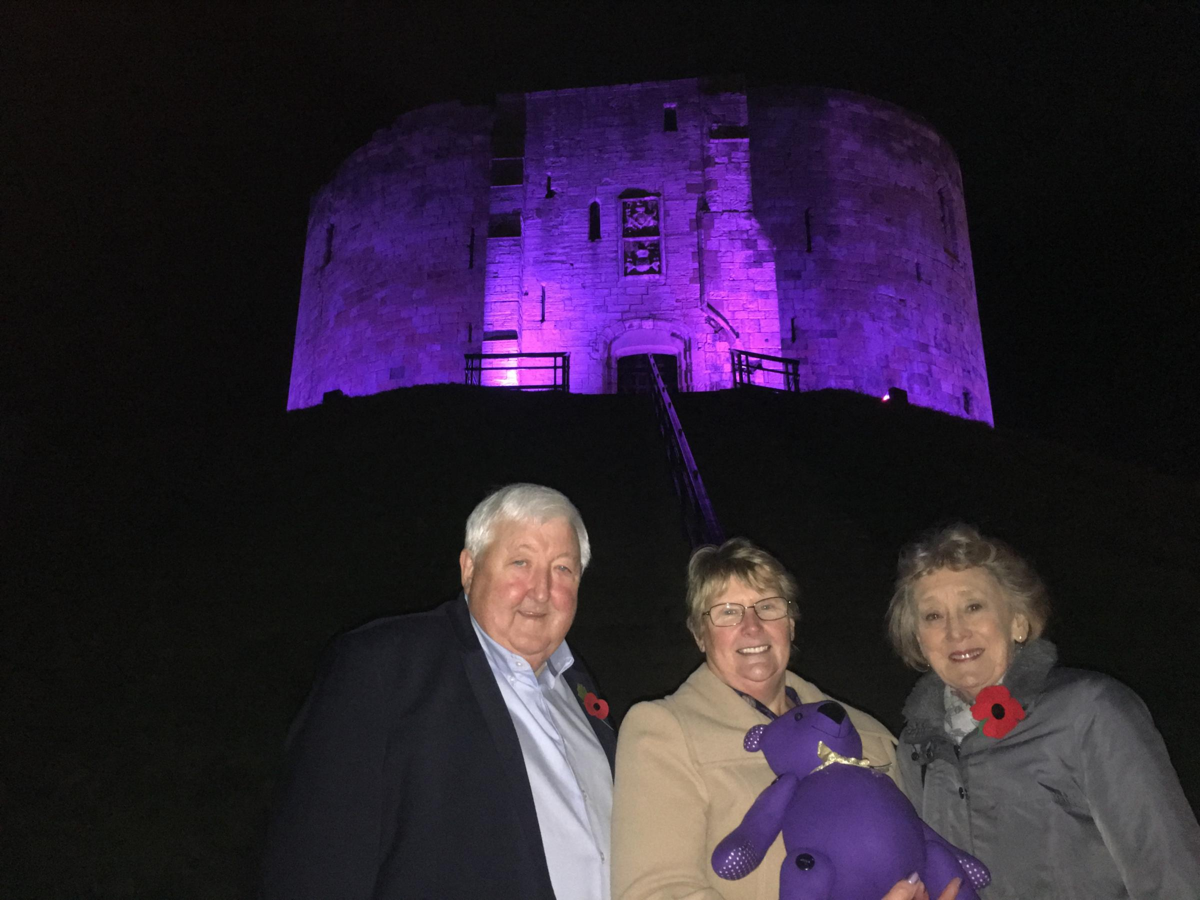 Cllr Ian Gillies, Jean Clark and Cllr Carol Runciman at Clifford's Tower, which is bathed in purple light