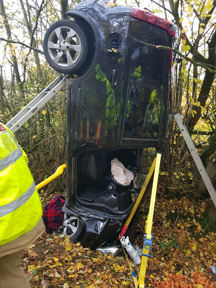 A picture tweeted by firefighters of the car which landed vertically down an embankment
