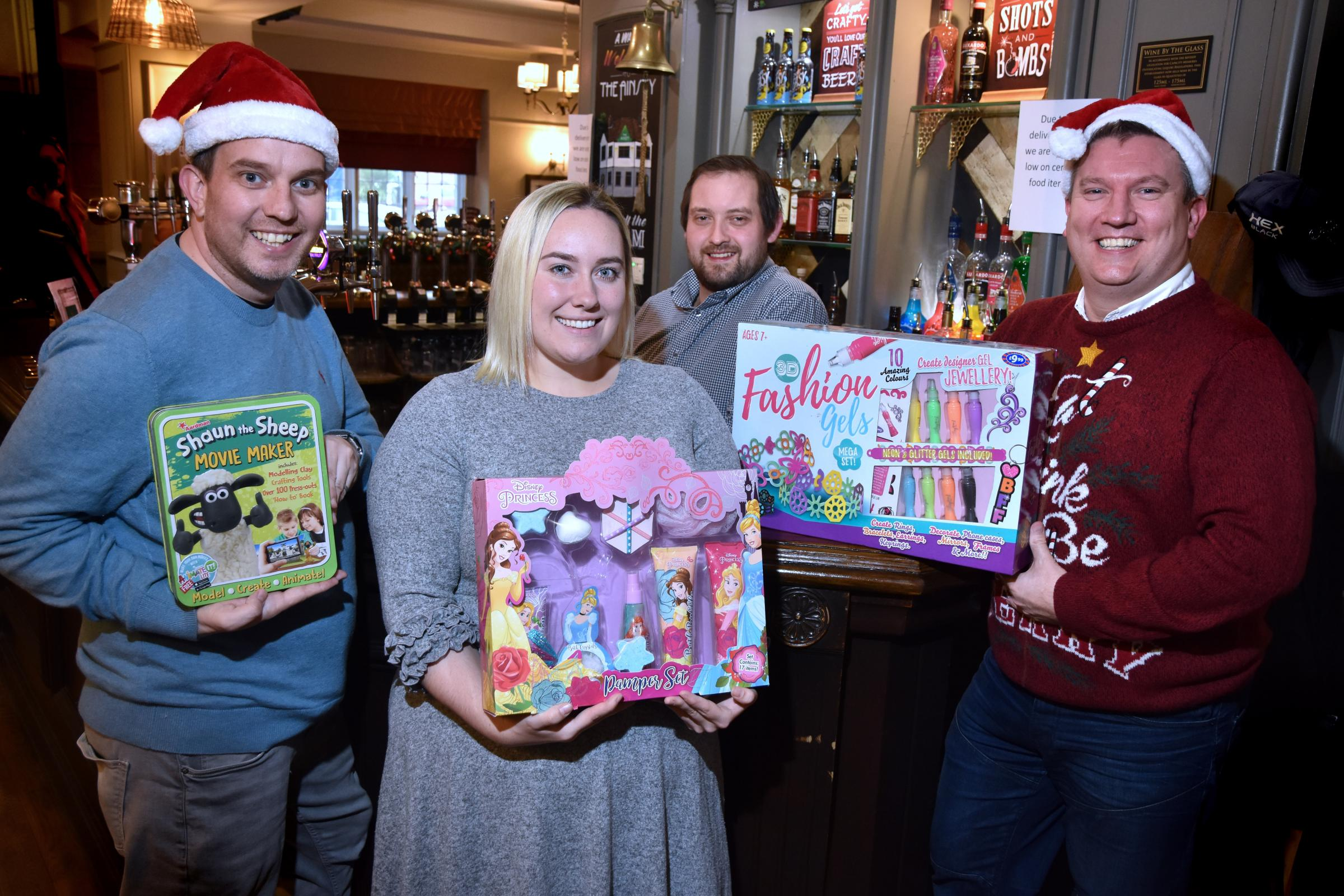 CHRISTMAS SPIRIT: The Ainsty Pub is one of the pubs where Christmas presents can be handed in for IDAS. Pictured, from left, Matt Lloyd, of YO1 Radio, Claudia Kilmartin, from IDAS, JP  Harrison, assistant manager at The Ainsty, Chris Marsden, of YO1 Radio