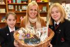 Heather Atkinson, from York Against Cancer, with Isobel Ovenden, left, and her sister Mollie, right, with the Christmas hamper raffle prize for the Shepherd Group Brass Band concert at Manor CE Academy. Picture: David Harrison