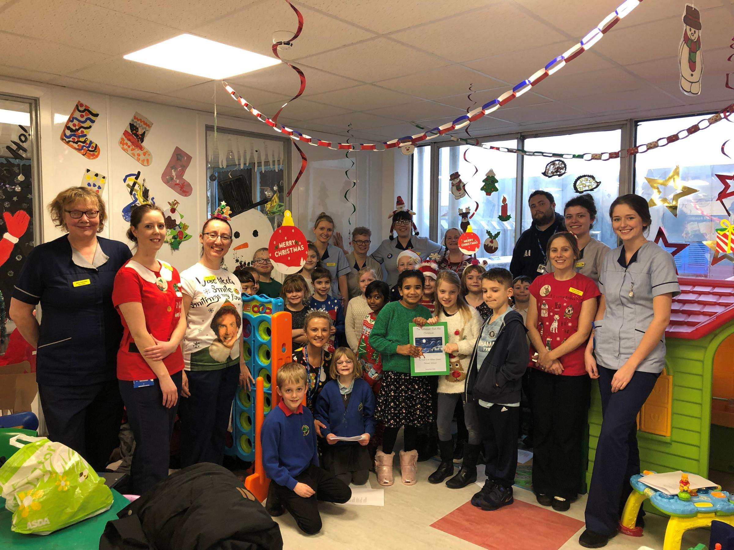 Leanne Haycock (2nd left) with staff and children on the Children's Ward and Clifton Green Primary School who brought gifts and performed their Christmas songs on the ward