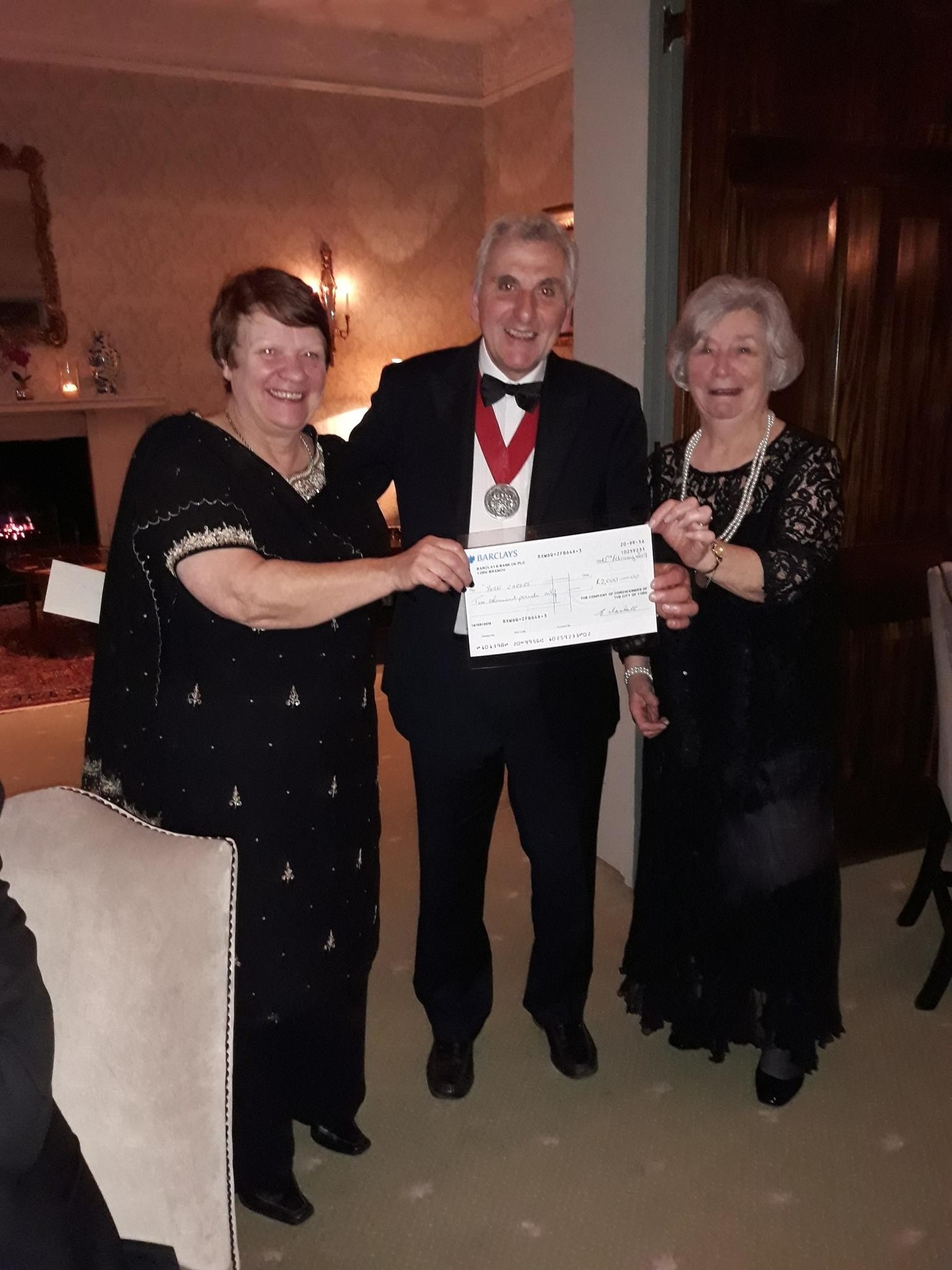 The Master of the Company of Cordwainers of the City of York, John Apps, handing over a £2000 cheque to York Young Carers' chair of trustees, Rosemary Temple and trustee Jackie Chapman
