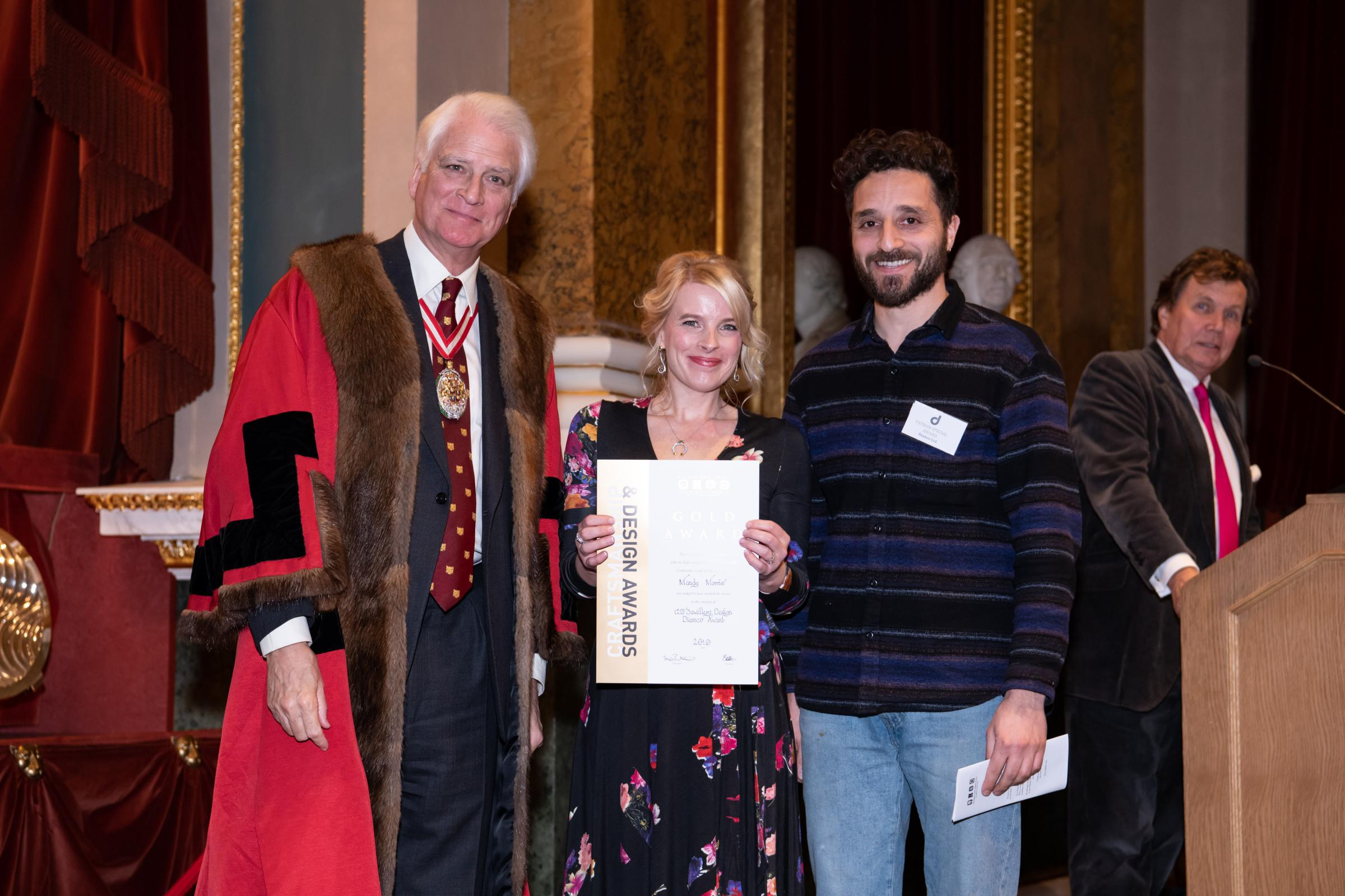 Mandy Morris, of Werk by TCJ Designs, receives her gold award from Goldsmiths' prime warden Micheal Prideaux (left) and a representative of award sponsor Diamco