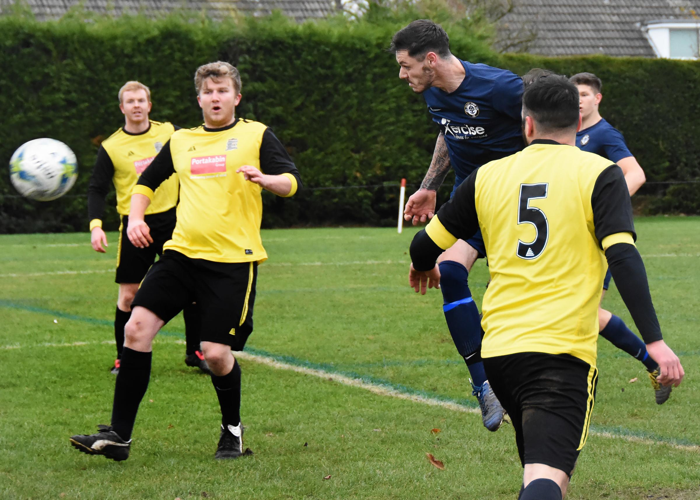 TREBLE: Adam Chaplin, in blue, whose hat-trick for Haxby Town helped to keep Riccall United in the relegation mire in division one of the York Minster Engineering League