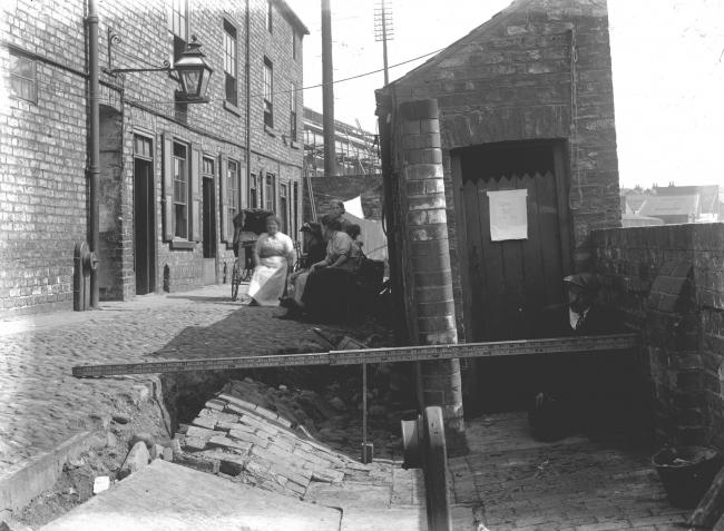 These women are at the foot of Dennis Street in June 1922. The houses were demolished in the late 1930s. The man is in front of an outdoor toilet which has a sign on it reading